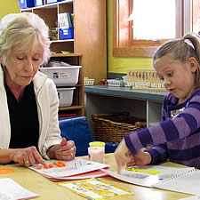 Woman working with elementary school child