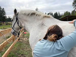 Methow Valley Riding Unlimited participant hugging a white horse.