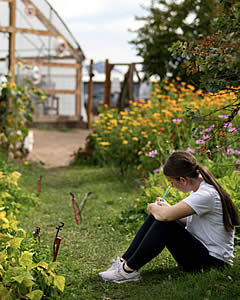 LBHS student studying in the school garden among the flowers.