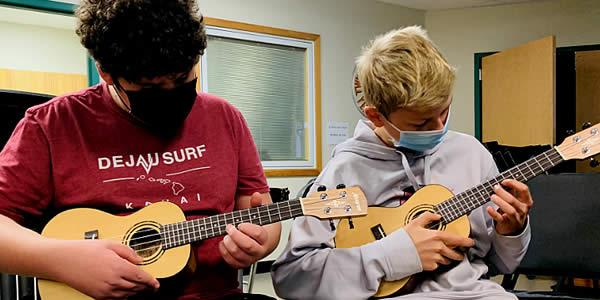 Two music students playing ukuleles.